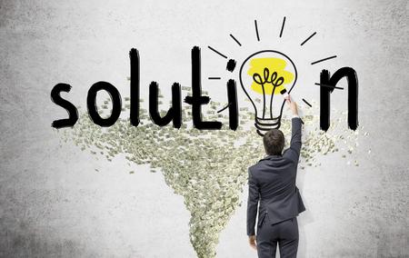 """Hombre de negocios joven que pinta una bombilla de color amarillo brillante con un pincel en la palabra """"solución"""" en lugar de la segunda 'o' en la pared blanca. Tornado Dólar debajo. Vista trasera. Concepto de la búsqueda de una solución."""