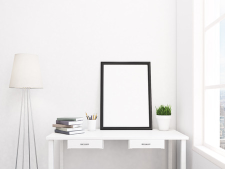 lamp: Big blank frame on the table leaning on the wall, satndard lamp nearby, pot with a plant, pencils and books on the table, window with city view to the right. Front view. Concept of exhibition. Stock Photo