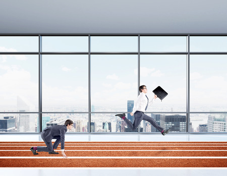 crouch: Two young businessmen competing on the track. One in crouch start, the other running forward with a black folder. Paris view in the window at the background. Concept of competition.