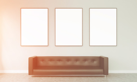 brown leather sofa: Three blank frames hanging over a brown leather sofa. Concrete background. Front view, filter. Concept od exhibition.