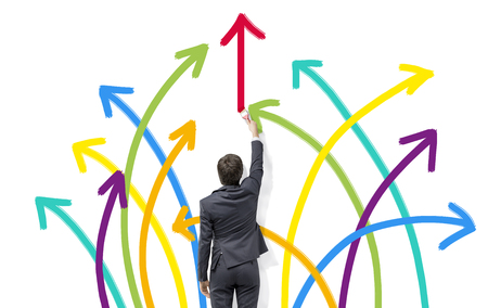 A businessman painting many arrows of different colours arranged as a firework on a white wall. Back view. Concept of diversity. Stockfoto
