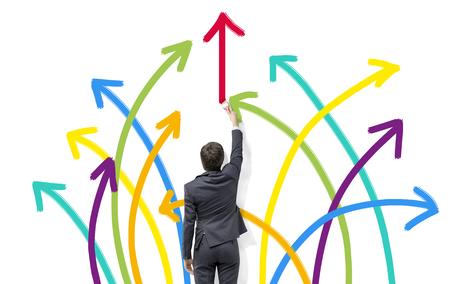 flechas direccion: Un hombre de negocios que pinta muchas flechas de diferentes colores dispuestos como un fuego artificial en una pared blanca. Vista trasera. Concepto de la diversidad. Foto de archivo