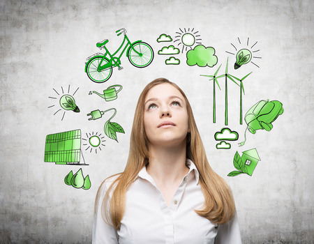 alternative energy sources: A woman looking up and dreaming, symbols of alternative energy sources painted in green colours on a white poster behind her. Concept of clean environment.
