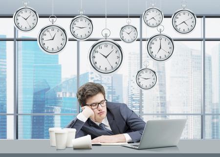 cansancio: Un hombre de negocios que duerme en el lugar de trabajo con la cabeza en la mano, portátil abierto en el frente, relojes de bolsillo se cierne desde arriba, ventanal con vista Singapur en el fondo. Concepto de cansancio