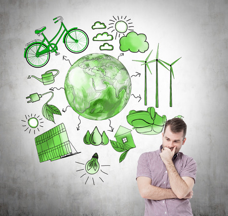 environment issues: A man with hand on his chin thinking about energy, symbols of alternative energy sources painted in green colours on a concrete wall. Green Earth in the middle. Concept of clean environment Stock Photo