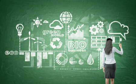 A woman drawing symbols of alternative energy sources on a green blackboard. Back view. Concept of clean environment.