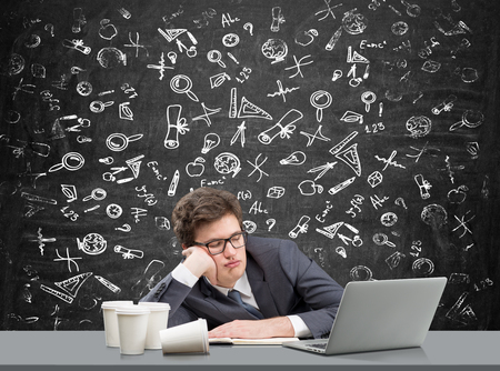 fulfilment: businessman sleeping at working place with his head on hand, open laptop in front of him, several glasses of coffee to the left, blackboard with science icons at the background. Concept of tiredness