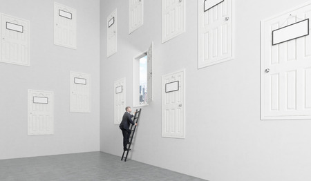 way out: A room with numerous closed doors in the walls at different height with blank door-plates on them, one is open, man climbing a ladder to get to it. Concept of finding a way out.