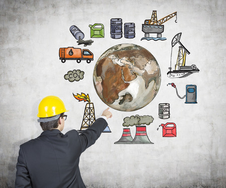monopoly: A man in a yellow helmet pointing at pictures arranged in a circle symbolizing stages of oil production. Brown Earth in the centre. Concrete background. Concept of environmental pollution.