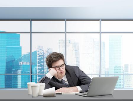 cansancio: empresario de dormir en el lugar de trabajo con la cabeza en la mano, portátil abierta por delante, varios vasos de café a la izquierda, ventanal con vista Singapur en el fondo. Concepto de cansancio