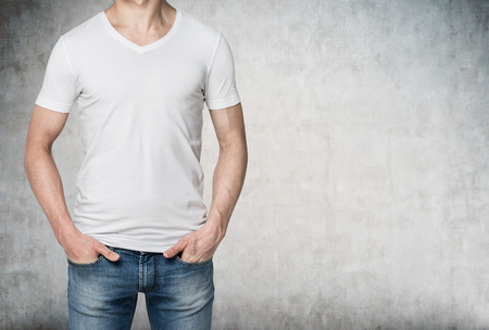 self assured: Man in a white T-shirt and jeans with hands in pockets, no face. Concrete background. Front view. Concept of casual clothes. Stock Photo