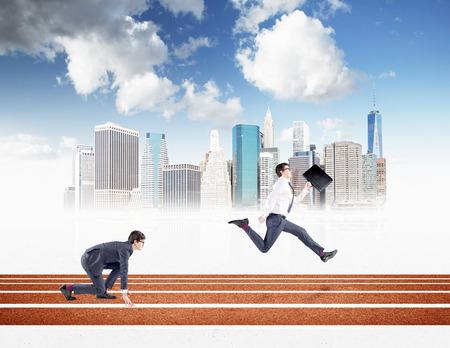 Dos hombres de negocios jóvenes que compiten en la pista. Uno de cada salida agachada, el otro corriendo hacia adelante con una carpeta negro. Nueva York y el cielo azul en el fondo. Concepto de competencia.