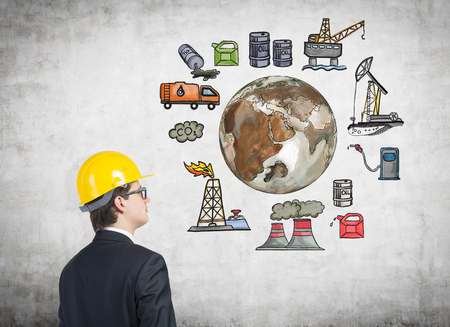 disaster supplies: A man in a yellow helmet looking at pictures arranged in a circle symbolizing stages of oil production. Brown Earth in the centre. Concrete background. Concept of environmental pollution.