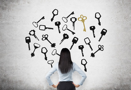 smart goals: Young woman with hands on hips in search of the right solution which are presented as keys around her. Concrete background. Back view. Concept of finding a solution. Stock Photo
