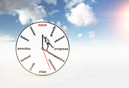 coping: Big clock with words instead of numbers, a man standing on clock hands, blue sky and sky at the background. Concept of coping with tasks on time.