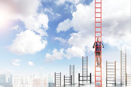 Un joven hombre de negocios en un traje subiendo por una escalera roja, muchas otras escaleras de atrás, vista a la ciudad y el cielo azul en el fondo. Concepto de desarrollo de la carrera.