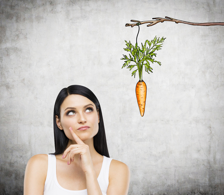 additional compensation: A young pretty woman with her hand on chin looking up at a painted carrot tied to a branch. Concrete background. Front view. Concept of reward.