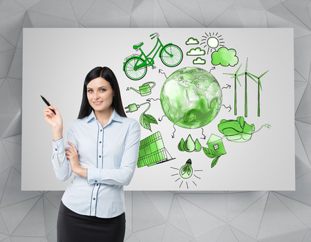 A woman with a pen in hand, symbols of alternative energy sources painted in green colours on a white poster behind her. Green Earth in the middle. Concept of clean environment