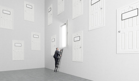 A room with numerous closed doors in the walls at different height with blank door-plates on them, one is open, man climbing a ladder to get to it. Concept of finding a way out.
