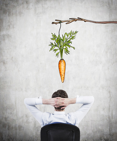 additional compensation: A young businessman with his hands on the back of his head sitting on the chair and looking at a painted carrot hanging from above. Concrete background. Back view. Concept of reaching an aim.