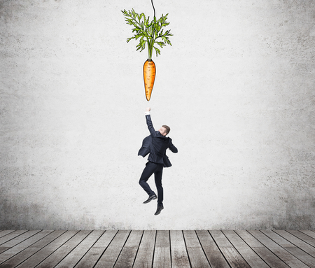 additional compensation: A young businessman jumping trying to reach a painted carrot hanging from above. Concrete background. Concept of reaching an aim.