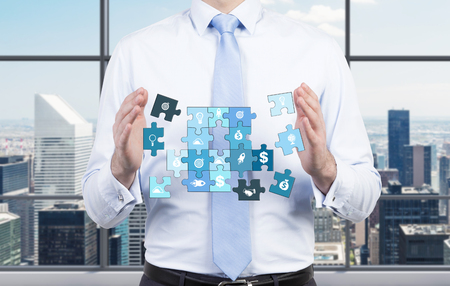 puzzle background: A man holding a puzzle of different life components, several parts missing. Front view, no face. City view at the background. Concept of getting a full picture. Stock Photo
