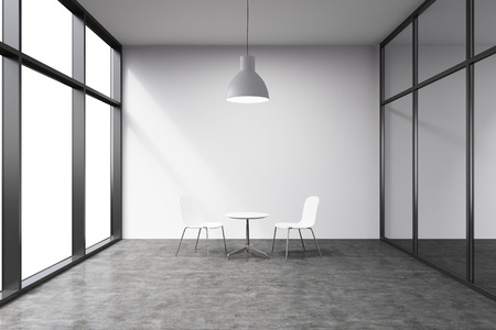 Empty office in a skyscraper, French window to the left, blanck white wall. A small white table and two white chairs at the wall, lamp above. Concept of talks. Stock Photo
