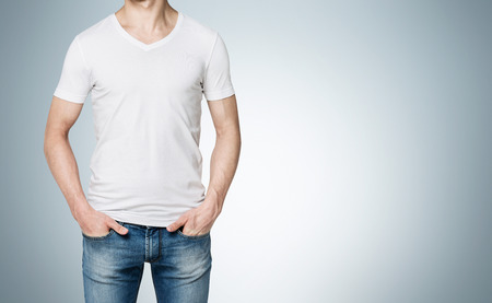 self assured: Man in a white T-shirt and jeans with hands in pockets, no face. Grey background. Front view. Concept of casual clothes.