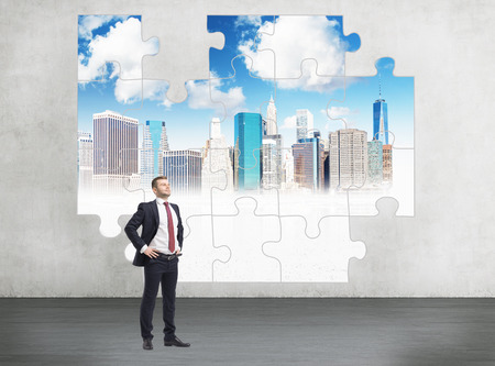 A young businessman with raised head and hands on hips standing in front of a puzzle of New York on a concrete wall. Concept of getting a full picture. Stock Photo