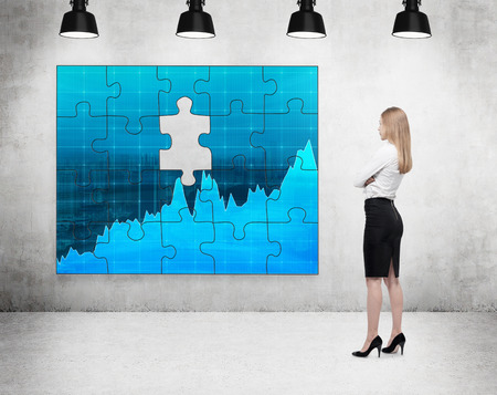 A businesswoman standing with arms crossed in front of a puzzle on the concrete wall with a picture of blue graphs, one part missing, four lamps on the ceiling. Concept of getting the full picture. Stock Photo