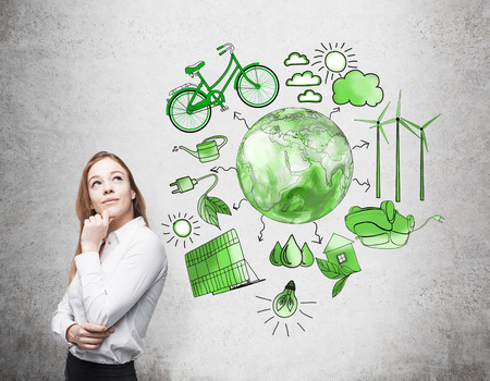 alternative energy sources: A woman with her hand to the chin thinking, symbols of alternative energy sources painted in green colours on a white poster behind her. Green Earth in the middle. Concept of clean environment.