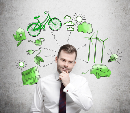 A man with his hand to the chin thinking, symbols of alternative energy sources painted in green colours on a white poster behind him. Concept of clean environment.