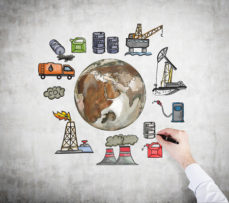 A hand painting pictures symbolizing stages of oil production  arranged in a circle. Brown Earth in the centre. Concrete background. Concept of environmental pollution.