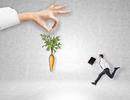 A hand holding a painted carrot tied to a branch, a young businessman with a folder running to it. Concrete background. Concept of reward.