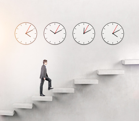 career timing: A serious young man going upstairs slowly, but with determination, four clocks on the white wall over seven steps. Concept of career growth. Stock Photo