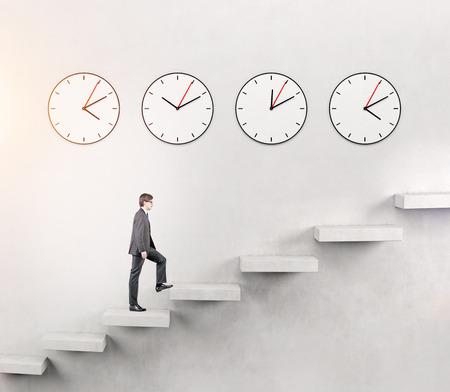 slowly: Un hombre joven serio que va arriba lentamente, pero con determinación, cuatro relojes en la pared blanca en siete pasos. Concepto de crecimiento de la carrera.
