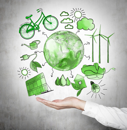 alternative energy sources: A hand holding symbols of alternative energy sources painted in green colours on a concrete wall. Green Earth in the middle. Concept of clean environment. Stock Photo