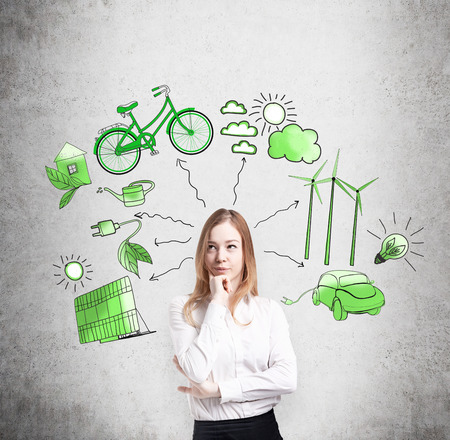 alternative energy sources: A woman with her hand to the chin thinking, symbols of alternative energy sources painted in green colours on a concrete wall behind her. Concept of clean environment. Stock Photo
