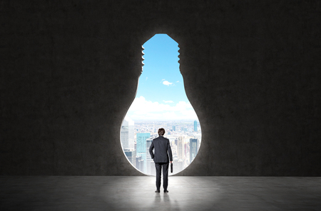 new horizons: businessman with a case in hand standing in front of a huge keyhole of the bulb shape ready to make a step forward. New York seen in the hole. Back view. Concept of opening new horizons. Stock Photo