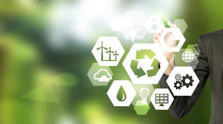 ecology  environment: hand drawing signs of different green sources of energy in hexahedron shape, a reduce, reuse, recycle sign in the centre. Blurred green background. Concept of clean environment. Stock Photo