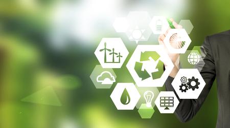 """Handzeichnung Zeichen der verschiedenen grünen Energiequellen in Hexaederform, eine """"Reduce, Reuse, Recycle"""" Zeichen in der Mitte. Verschwommene grünen Hintergrund. Konzept der sauberen Umwelt. Standard-Bild"""