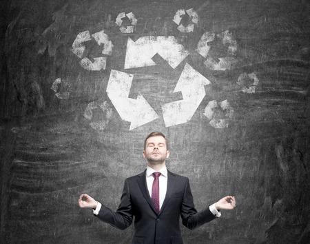"""reduce reutiliza recicla: hombre de pie delante de la pizarra con las manos levantadas, como si en una postura de meditaci�n, con los ojos cerrados. A ', reutilizar y reciclar, reducir la """"se�al grande sobre su cabeza. Vista frontal. Concepto de energ�a limpia. Foto de archivo"""