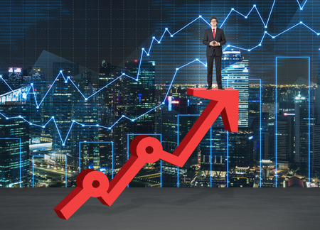 aim: A young man standing and thinking on a thick red growing graph looking in front with his hands in front. Night city and graphs at the background. Front view. Concept of success.