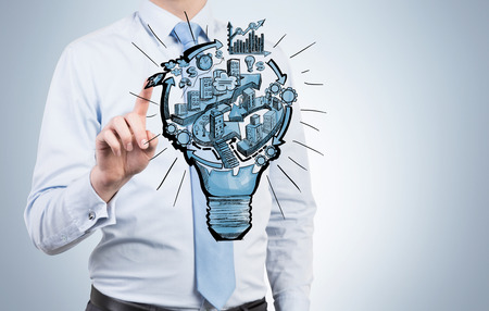 greyish: A man touching a picture of a bulb with stages of organizing a business process in it. Greyish background. Front view. No face. Concept of running a business. Stock Photo