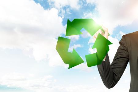 reduce reutiliza recicla: hombre en un juego de dibujo a ', reutilizar y reciclar, reducir el' cartel verde con una pluma verde. No cara. cielo azul con nubes en el fondo. No cara. Concepto de medio ambiente limpio. Foto de archivo