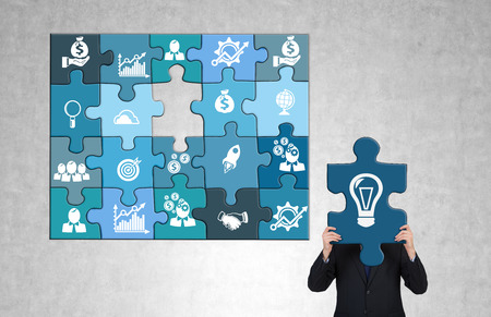 A man gathering a blue business puzzle with business icons on each part. The man holding the last bulb part missing so that he hides head behind it. Greyish background. Concept of doing business. Stock Photo
