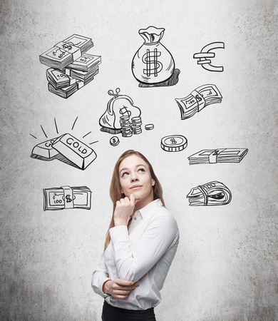 wealth: beautiful woman with hand on chin looking up and thinking about money, black pictures symbolizing money over her head. Concrete background. Front view. Concept of running into money. Stock Photo