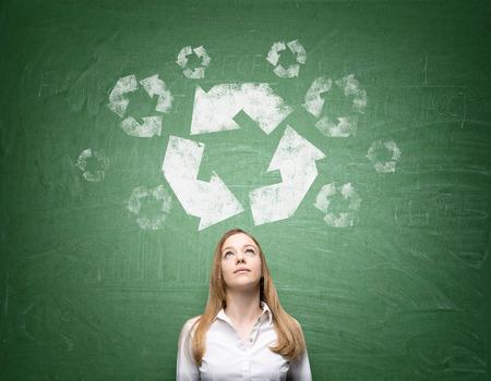 """reduce reutiliza recicla: mujer de pie o delante? una pizarra verde con los ojos hacia arriba. A ', reutilizar y reciclar, reducir la """"se�al grande sobre su cabeza. Vista frontal. Concepto de energ�a limpia."""
