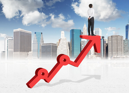 A young man standing and thinking on a thick red growing graph looking in front with his hands at the back. New York and blue sky at the background. Back view. Concept of success. Stock Photo