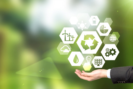 clean background: hand holding signs of different green sources of energy in hexahedron shape, a reduce, reuse, recycle sign in the centre. Blurred green background. Concept of clean environment. Stock Photo